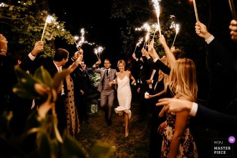 PACA Photojournaliste de mariage | Les mariés en France quittent leur réception de mariage pour des invités tenant des étincelles