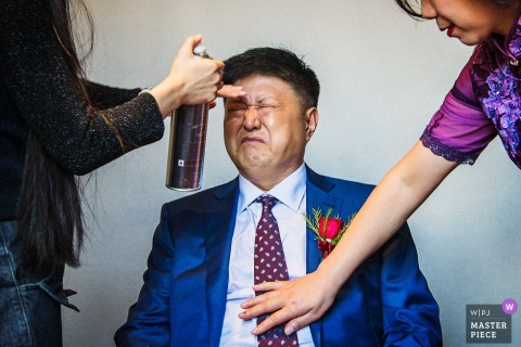 Zhengzhou Wedding Photojournalist | preparing the man for the wedding ceremony with hairspray and tie fixing