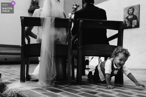 Pau, France Photojournaliste de mariage | un petit garçon rampe sous la chaise des mariés pendant la cérémonie