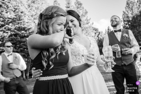 Una giovane donna è sopraffatta dall'emozione mentre fa un discorso a questo matrimonio all'aperto a Foresthill, in California