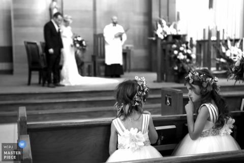 Indiana trouwfoto | twee bloemmeisjes die stil proberen te zijn tijdens de kerkhuwelijksceremonie