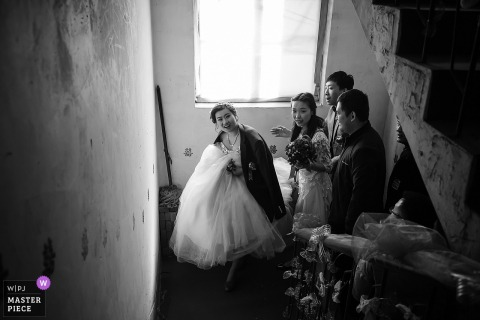 Shanxi Wedding Photojournalist | China actual day wedding photography in black-and-white - bride climbing stairwell with family
