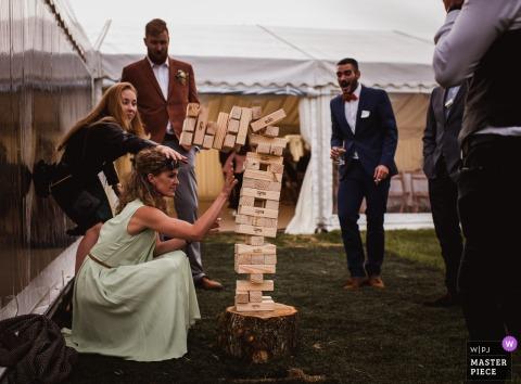 Fotoperiodista de bodas de Wilkswood | Recepción al aire libre con una carpa e invitados jugando a Jenga.