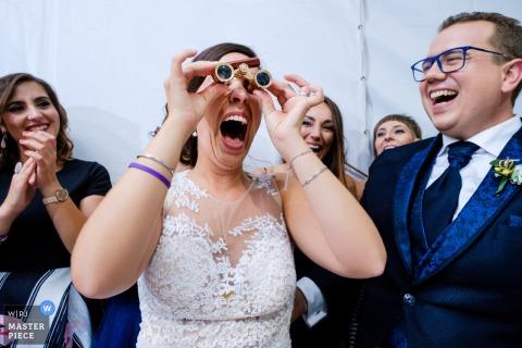 Muro Wedding Fotojournalist | de bruid plaats met mini-verrekijker op de bruiloft