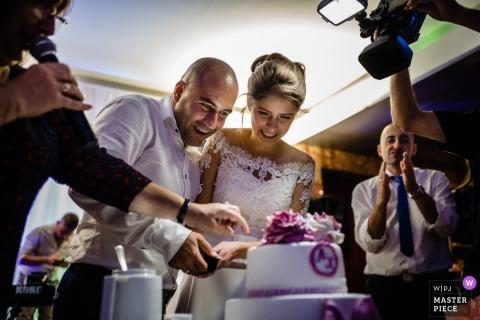 Lovech Wedding Fotojournalist | De bruid en de bruidegom van Bulgarije snijden hun huwelijkscake bij de ontvangst