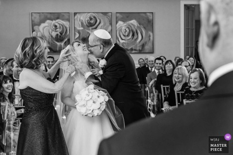 New Jersey Wedding Photojournalist | Black and white ceremony photo of The father kissing his daughter, the bride