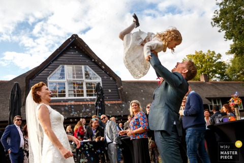 Netherlands outdoor wedding reception - barchem groom lifts a young flower girl into the air as the bride looks on