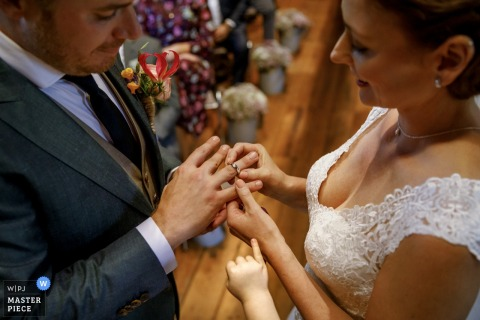 Barchem Wedding Photo | the bride places the ring on the grooms finger during the wedding ceremony