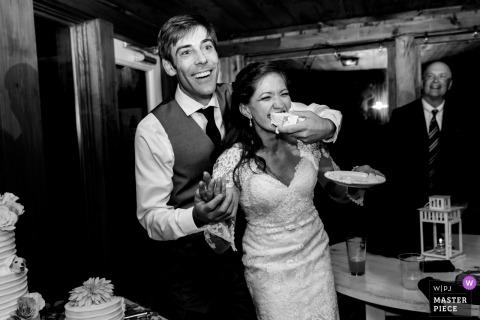 De bruidegom geeft de bruid op creatieve wijze een plak cake bij hun bruiloftsreceptie Linekin Bay Resort Boothbay Harbor Maine
