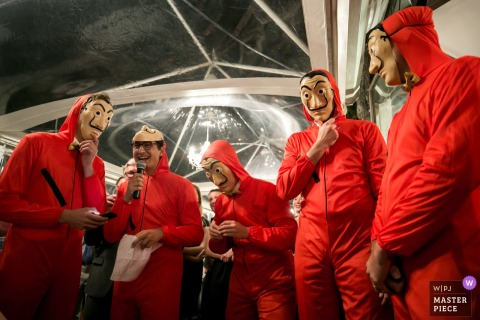 Florence, Italy Wedding Photojournalist | groomsman dressed in red suits with masks in the reception tent