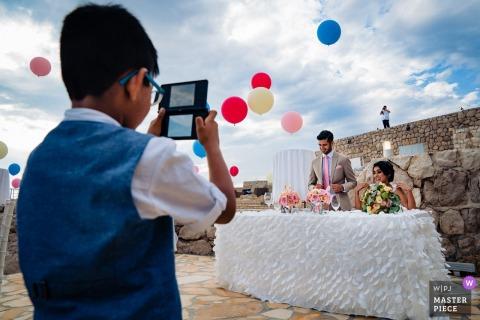 Kroatië Wedding Fotojournalist | een jonge jongen neemt een foto van de bruid en de bruidegom aan de hoofdtafel met ballonnen