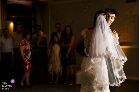 Bucharest Wedding Photojournalist | the groom smiles as he dances with his new bride at the wedding reception