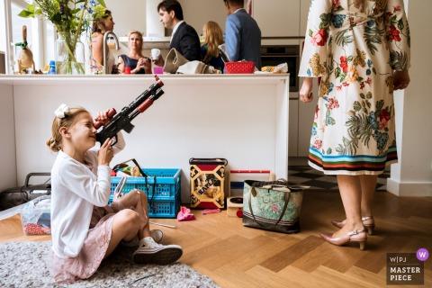 een bloemenmeisje speelt met een stuk speelgoed pistool op een bruiloft in Haarlem - Nederland