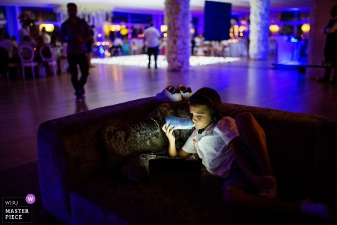 Guimarães, Portugal Wedding Photojournalist | a boy plays video games during the colorful reception party