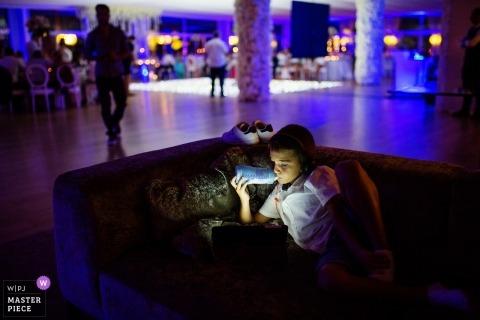 Guimarães, Portugal Trouwfotojournalist | een jongen speelt videogames tijdens de kleurrijke receptie