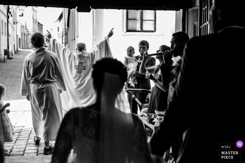 Prague Wedding Photojournalist | the priest leads the way for the bride and groom at their Czech Republic wedding