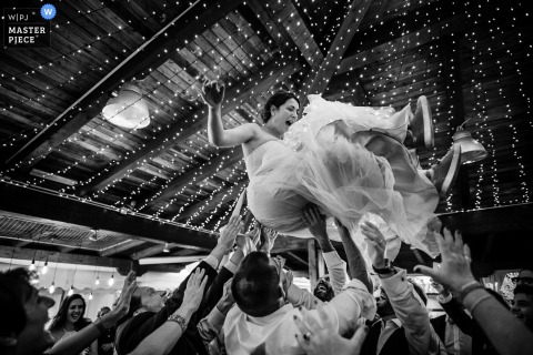 Sardinia Wedding Photos | Cagliari reception party Image with the bride being thrown into the air