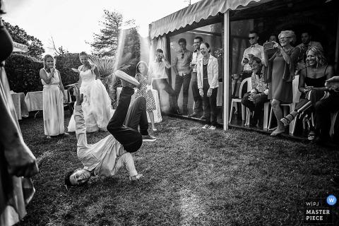 Antico Casale Borgofranco wedding photograph of break dancing guest on the grass.