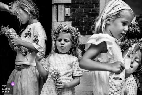 Waasmunster Wedding Photojournalist | bloemenmeisjes die van hun zoete giften op huwelijksdag genieten