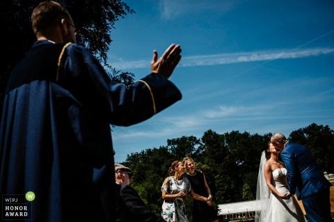 arnhem Guests watch as bride and groom kiss to make their outdoor ceremony official