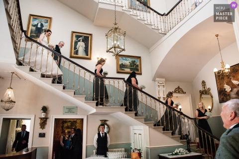 Melville Castle, Edinburgh, Schottland Hochzeitsfoto der Brautjungfern, der Braut und des Vatis, die die Treppe hinunterkommen