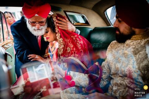 Londen, UK bruid omarmt haar vader op de achterkant van de vintage limousine