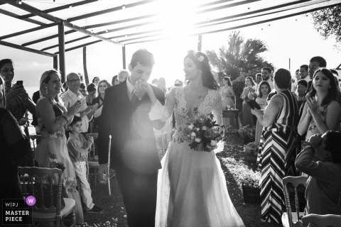 Rio de Janeiro/RJ - Brazil sun flared ceremony photograph in black-and-white with the groom kissing the bride's hand as she holds her bouquet of flowers