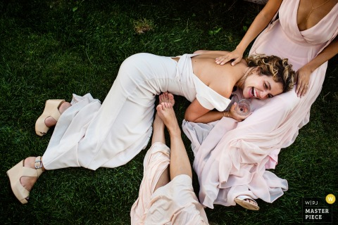 Falmouth, MA bridesmaids have fun and laugh with the bride on the grass