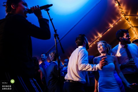 Bride and groom on the dance floor near the wedding Singer at this Falmouth, MA reception with blue lighting