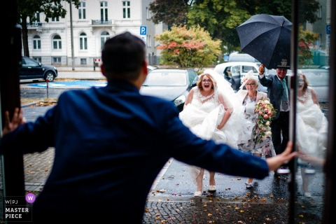 A gentleman holds the door open for a bride in a hurry to get in out of the rain in Hamburg, Germany