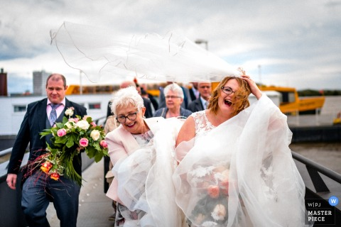 Hamburg, Germany Wedding Photojournalist | the bride laughs as the wind blows her veil