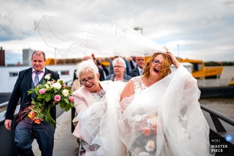 Fotojournalist van de bruiloft in Hamburg, Duitsland de bruid lacht terwijl de wind haar sluier blaast