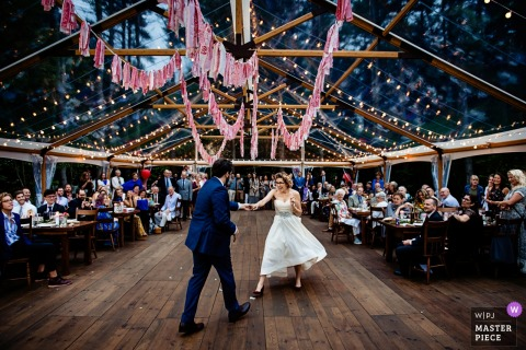 Putney, Vermont Wedding Photojournalist | clear panel tent covers this vintage wooden dance floor at the reception - bride and groom dancing solo