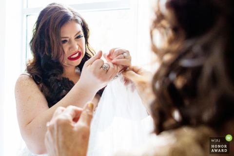 La mariée fait une grimace en essayant de déchirer le fil de la robe de mariée - Le pavillon à la maison en pierre Stirling Ridge nj wedding