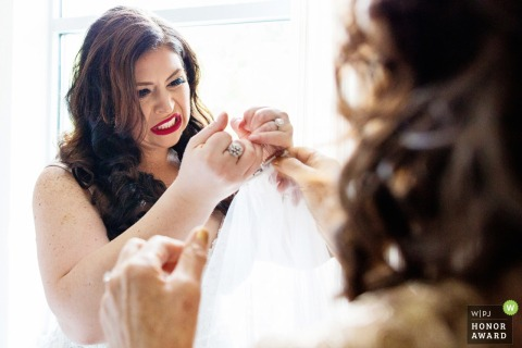 The bride makes a face as she tries to rip thread off wedding gown - The lodge at stone house stirling ridge nj wedding