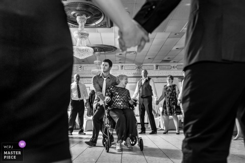 Plymouth, Michigan Wedding Photojournalist | Black and white photo of guests dancing in a circle holding hands