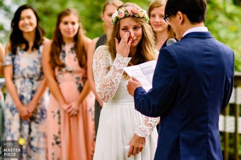 Croton Point Park NY trouwfoto van de bruid huilen terwijl de bruidegom zijn geloften leest.