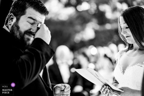De Smokehouse bij de Airlie, VA-huwelijksfoto van de bruidegom afvegende scheuren tijdens openluchtceremonie.