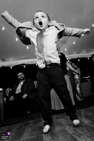 New Harbor Wedding Fotojournalist | een kleine jongen danst met hart op deze huwelijksreceptie in Maine in een tent