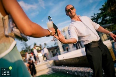 Ospiti che si godono lo champagne alla reception all'aperto della Thailandia