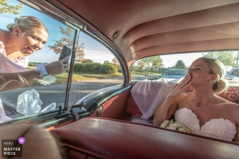 The bride blows kisses to A phone yielding a bridesmaid from the rear Seat of a vintage car in Plobsheim, France