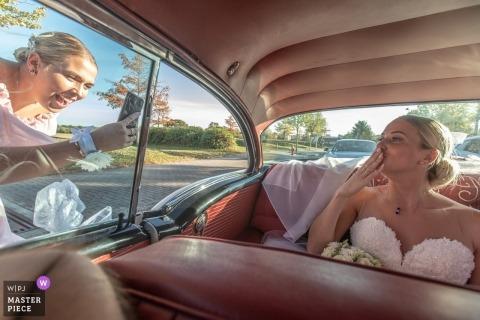 Panna młoda wieje pocałunki do telefonu, który daje druhnę z tylnego siedzenia zabytkowego samochodu w Plobsheim we Francji