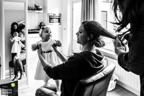 Bride holds flower girl while getting her hair ready in Netherlands