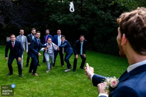 East Flanders Wedding Photojournalist | the groom shoots the garter to a group of single men at the outdoor wedding reception