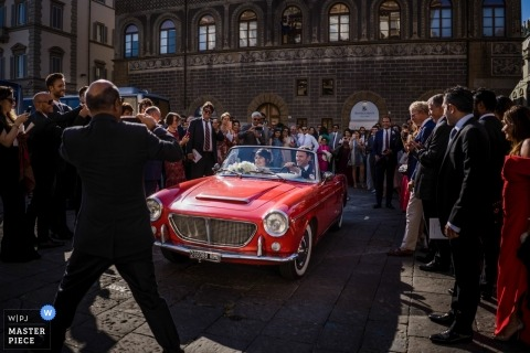 Florence Wedding photograph of the bride and groom departing in a vintage red convertible car