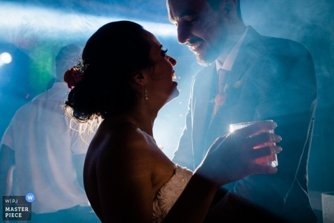 Macaé Wedding Photojournalist | Rio de Janeiro bride and groom dancing with drinks on a foggy reception dance floor