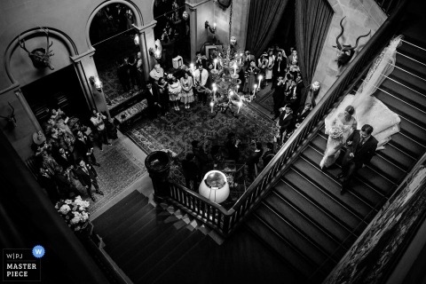 Eastnor Castle, United Kingdom wedding photograph of bride heading down the stairs at the reception