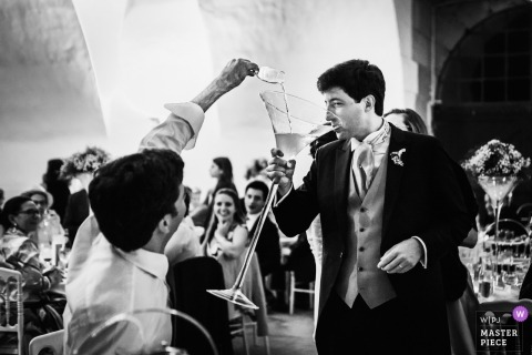 Bourgogne - France Wedding Photojournalist | the groom drinks from a very large Champagne glass at Île-de-France wedding reception