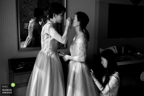 Bruidsmeisjes die de bruid helpen klaar te worden vóór de bruiloft - het bevestigen maakt omhoog en beëindigt raakt op de kleding