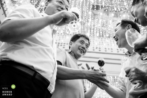 Guests enjoying drinks during the wedding reception in China - Black and white photography